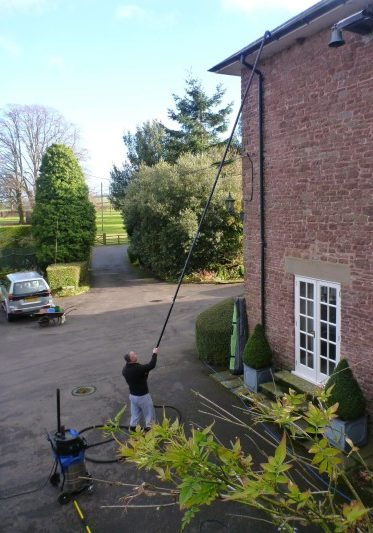 An image of a Ultimate Cleaning Solutions team member cleaning a gutter